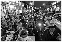 Street packed with motorcycles and vehicles at dusk. Ho Chi Minh City, Vietnam (black and white)