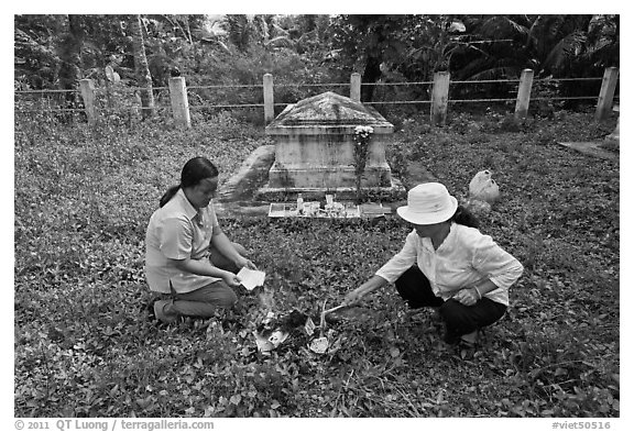 Women burning notes as offering in cemetery. Ben Tre, Vietnam (black and white)