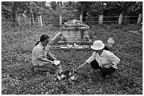 Women burning notes as offering in cemetery, Ben Tre. Mekong Delta, Vietnam (black and white)
