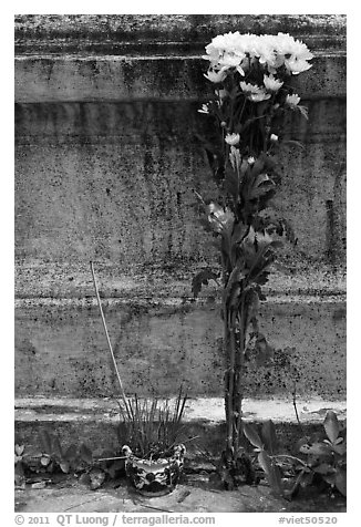 Incense and flowers next to tomb. Ben Tre, Vietnam (black and white)