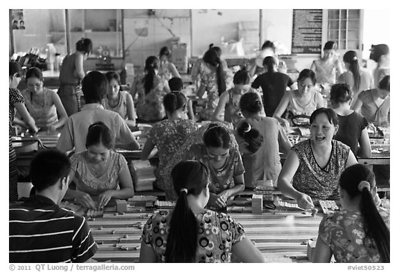 Women packing coconut candy in factory. Ben Tre, Vietnam (black and white)