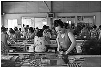 Woman cutting strips of coconut candy in factory. Ben Tre, Vietnam ( black and white)