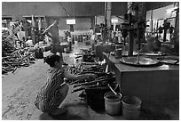 Woman feeding furnace in cococut candy factory. Ben Tre, Vietnam (black and white)