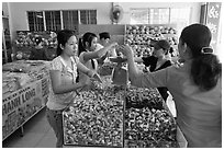 Women weighting coconut candy in retail store. Ben Tre, Vietnam (black and white)