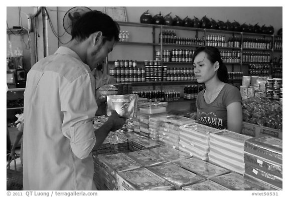 Customer buying box of coconut candy. Ben Tre, Vietnam (black and white)