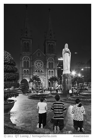 Family in prayer outside Notre-Dame Basilica at night. Ho Chi Minh City, Vietnam
