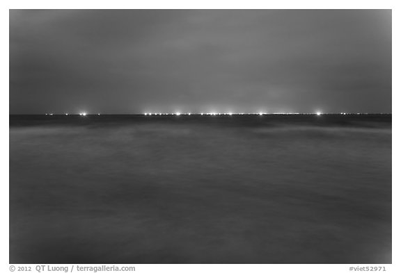 South China Sea at night with lights of fishing boats on horizon. Mui Ne, Vietnam (black and white)