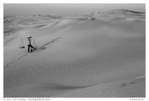 Red sand dunes and woman with carrying pole and baskets. Mui Ne, Vietnam (black and white)