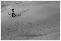 Woman walking with baskets on sands. Mui Ne, Vietnam (black and white)