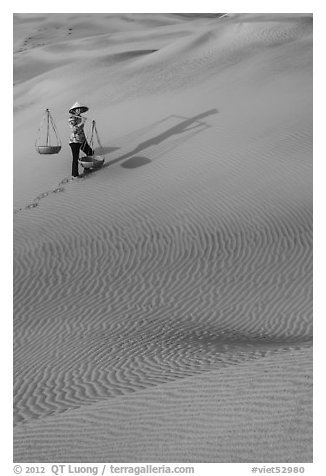 Woman with yoke baskets on sands. Mui Ne, Vietnam (black and white)