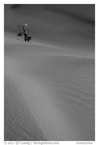 Woman with conical hat and shoulder pole baskets pauses on dune. Mui Ne, Vietnam (black and white)