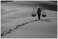Woman walking on sand with two shoulder baskets. Mui Ne, Vietnam (black and white)