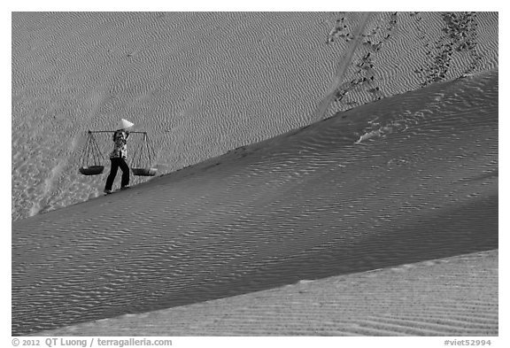 Woman ascending dune ridge with two baskets. Mui Ne, Vietnam (black and white)