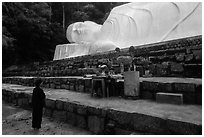 Woman prays below reclining Buddha statue. Ta Cu Mountain, Vietnam (black and white)