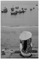 Woman with conical hat sitting above fishing fleet. Mui Ne, Vietnam (black and white)
