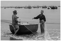 Man and woman gathering fishing net onto roundboat. Mui Ne, Vietnam (black and white)