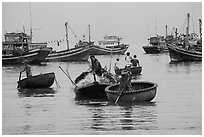 Men use round woven boats to disembark from fishing boats. Mui Ne, Vietnam (black and white)