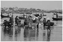 Fishing activity reflected on wet beach. Mui Ne, Vietnam (black and white)