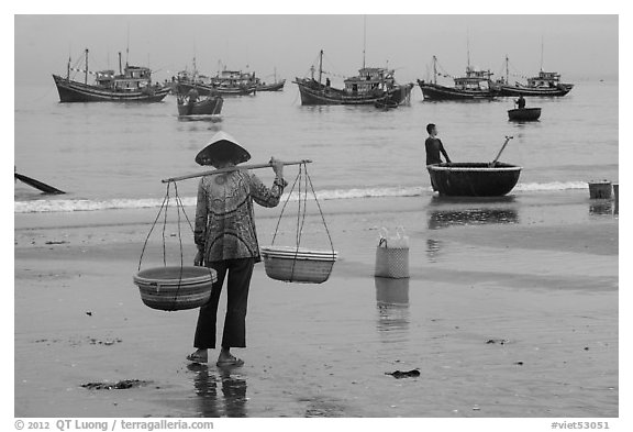 Woman with yoke baskets on beach. Mui Ne, Vietnam (black and white)
