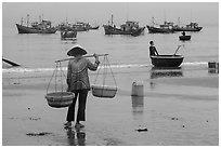 Woman with yoke baskets on beach. Mui Ne, Vietnam ( black and white)