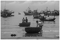 Fishermen on roundboats and fishing fleet. Mui Ne, Vietnam (black and white)
