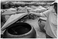 Woman examining vat of fish sauch. Mui Ne, Vietnam (black and white)