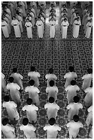 Men and women dressed in white stand in opposing rows in Cao Dai temple. Tay Ninh, Vietnam (black and white)