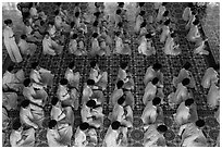 Worshippers dressed in white pray in neat rows in Cao Dai temple. Tay Ninh, Vietnam (black and white)