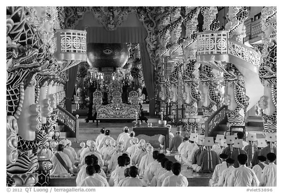 Dignitaries (in colored robes) and other followers praying at the Main hall, Cao Dai temple. Tay Ninh, Vietnam (black and white)