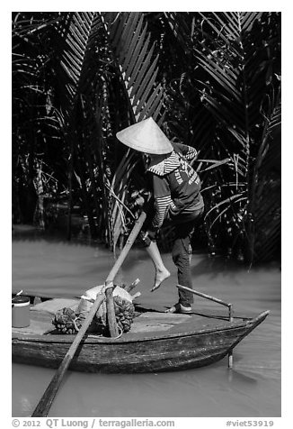 Woman standing in canoe on jungle canal, Phoenix Island. My Tho, Vietnam (black and white)