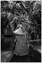 Woman rowing boat under jungle canopy, Phoenix Island. My Tho, Vietnam (black and white)