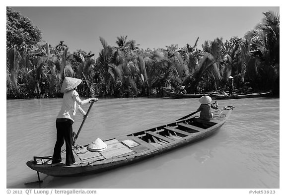 Women row canoes, Phoenix Island. My Tho, Vietnam (black and white)