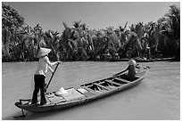 Women row canoes, Phoenix Island. Mekong Delta, Vietnam (black and white)