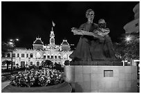 Ho Chi Minh as teacher bronze by Diep Minh Chau and City Hall by night. Ho Chi Minh City, Vietnam ( black and white)