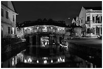 Covered Japanese Bridge reflected in canal by night. Hoi An, Vietnam (black and white)