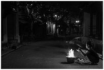 Woman burning paper on street at night. Hoi An, Vietnam ( black and white)