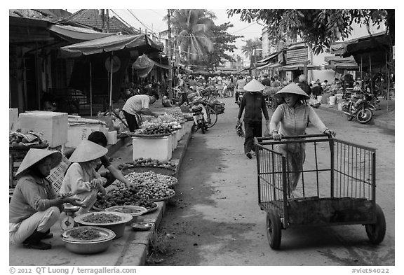 Woman pushing cart on market street. Hoi An, Vietnam (black and white)