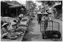 Woman pushing cart on market street. Hoi An, Vietnam ( black and white)