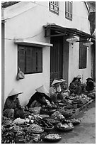 Vegetable vendors sitting in front of old house. Hoi An, Vietnam ( black and white)