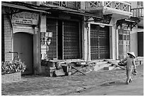 Woman carrying fruit in front of old storefronts. Hoi An, Vietnam ( black and white)