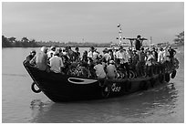 People crossing river on small ferry. Hoi An, Vietnam (black and white)