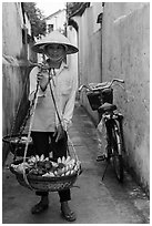 Fruit vendor carrying bananas. Hoi An, Vietnam ( black and white)