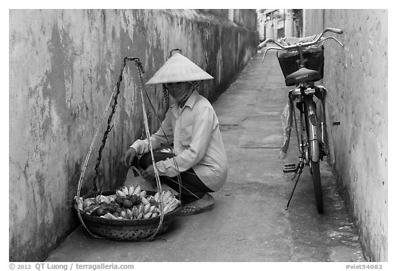 Fruit vendor in narrow alley. Hoi An, Vietnam (black and white)