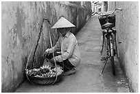 Fruit vendor in narrow alley. Hoi An, Vietnam ( black and white)