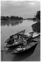 Family having dinner on boats at dusk. Hoi An, Vietnam (black and white)