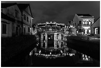 Japanese covered bridge reflected in canal at night. Hoi An, Vietnam (black and white)