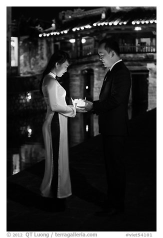 Couple holding candles in front of Japanese bridge at night. Hoi An, Vietnam (black and white)