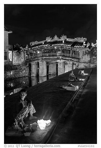 Candle vendors in front of Japanese bridge at night. Hoi An, Vietnam (black and white)