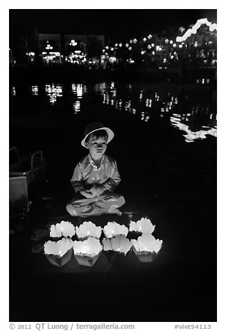 Boy selling candle lanterns by the river. Hoi An, Vietnam (black and white)