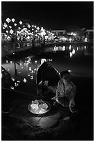 Woman selling candle lanterns by the bridge. Hoi An, Vietnam (black and white)
